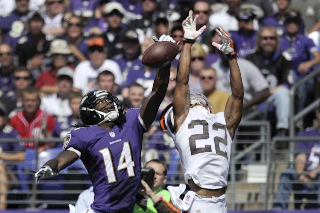 Baltimore Ravens wide receiver Marlon Brown (14) cannot hang on to a pass under pressure from Cleveland Browns cornerback Buster Skrine (22) during the first half of a NFL football game in Baltimore, Md., Sunday, Sept. 15, 2013. (AP Photo/Nick Wass)