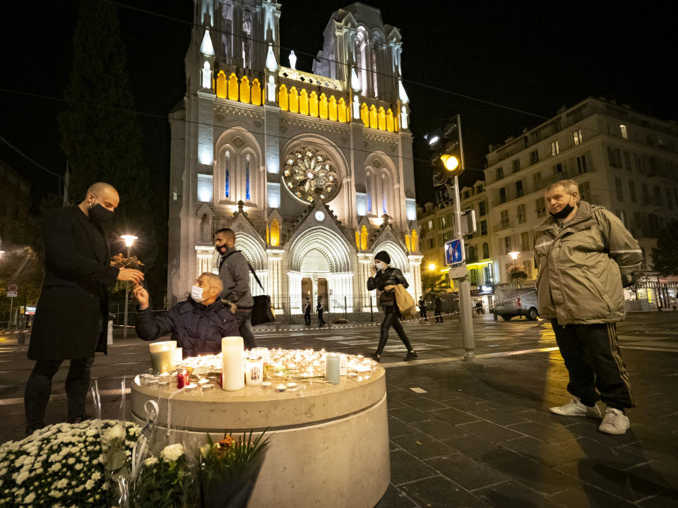 NICE, FRANCE - OCTOBER 29:  People pay tributes at night in front of Notre Dame Basilica on October 29, 2020 in Nice, France. A man armed with a knife fatally attacked three people in the Notre-Dame church in Nice, located in the heart of the city. (Photo by Arnold Jerocki/Getty Images)