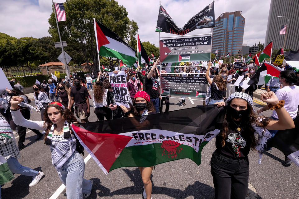 Demonstrators holding signs march to the Israeli Consulate during a protest against Israel and in support of Palestinians during the conflict in the Middle East, Saturday, May 15, 2021, in the Westwood section of Los Angeles. (AP Photo/Ringo H.W. Chiu)