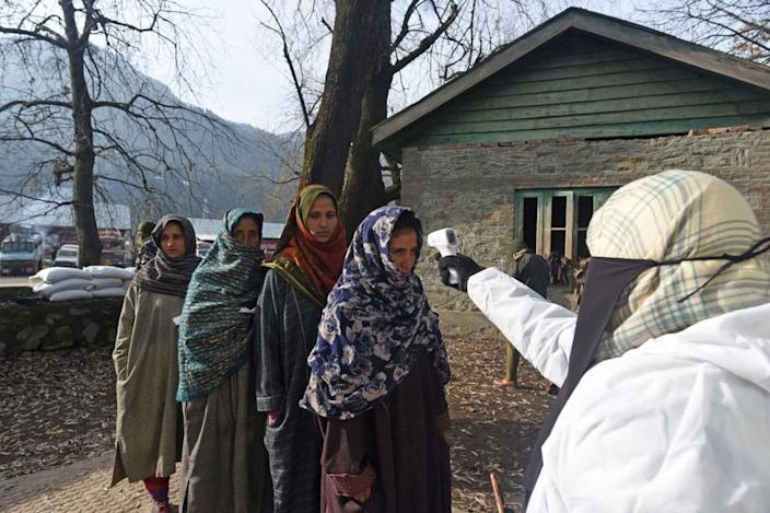 A health worker thermal screens voters arriving at a polling station to cast their vote.