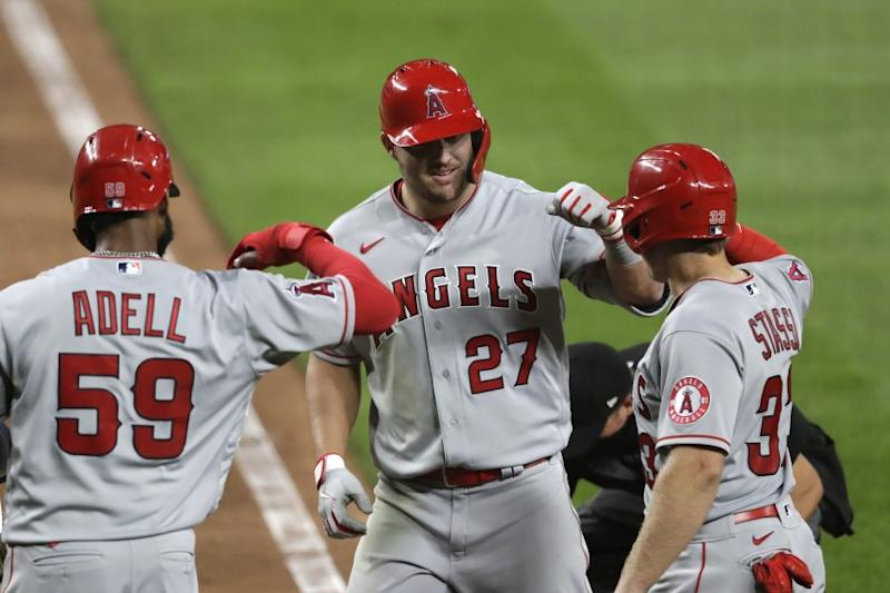 Los Angeles Angels' Mike Trout (27) is met at home by Jo Adell (59) and Max Stassi on his three-run home run against the Seattle Mariners during the seventh inning of a baseball game Wednesday, Aug. 5, 2020, in Seattle. (AP Photo/Elaine Thompson)