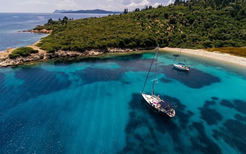 Aerial view of sail boats anchored in bay with crystal clear water, Meganisi Island Greece - Milijko