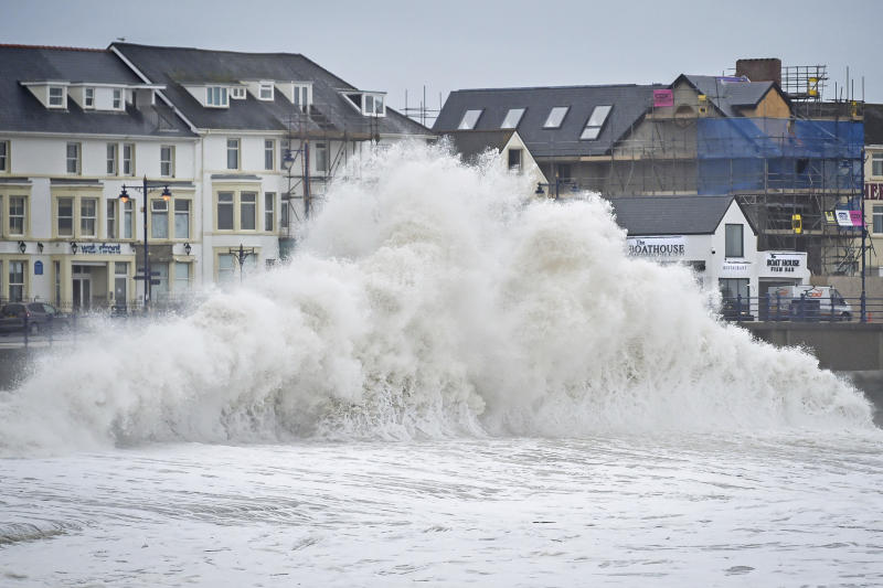 Huge waves hit the sea wall in Porthcawl, Wales, Tuesday Jan. 14, 2020, as gales of up to 80mph from storm Brendan caused disruption around the UK. (Ben Birchall/PA via AP)