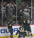 Minnesota Wild center Joel Eriksson Ek, second from right, celebrates his goal against the Vegas Golden Knights with left wing Jordan Greenway (18), defenseman Matt Dumba (24) and defenseman Jonas Brodin (25) during the first period in Game 3 of an NHL hockey first-round playoff series Thursday, May 20, 2021, in St. Paul, Minn. (Aaron Lavinsky/Star Tribune via AP)
