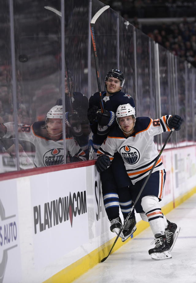 Winnipeg Jets' Jack Roslovic (28) is checked by Edmonton Oilers' Matt Benning (83) during second-period NHL hockey game action in Winnipeg, Manitoba, Sunday, Oct. 20, 2019. (Fred Greenslade/The Canadian Press via AP)
