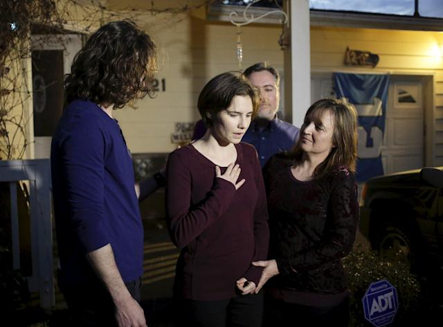 Amanda Knox (2nd L) talks to the press surrounded by family outside her mother's home in Seattle, Washington March 27, 2015. Italy's top court on Friday annulled the conviction of American Amanda Knox for the 2007 murder of British student Meredith Kercher and, in a surprise verdict, acquitted her of the charge. The Court of Cassation threw out the second guilty verdict to have been passed on Knox, 27, and her Italian former boyfriend Raffaele Sollecito for the lethal stabbing. REUTERS/Jason Redmond