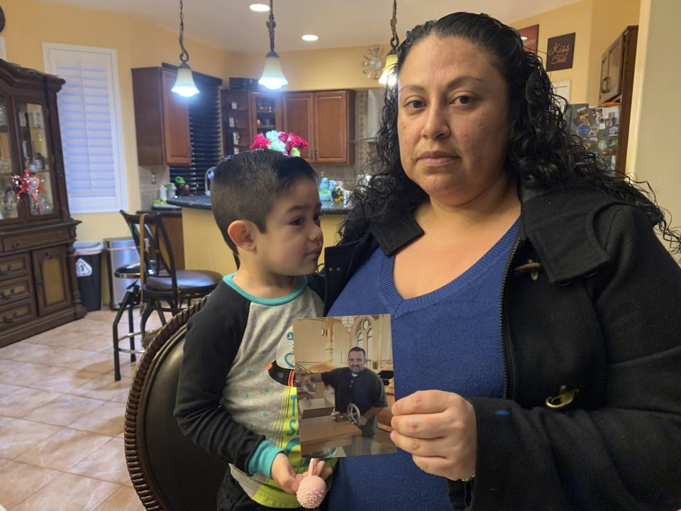 Nancy Espinoza, 37, sits with her 3-year-old son at their home in Corona, Calif., on Thursday, Jan. 28, 2021, while holding a photo of her husband Antonio Espinoza, who died of COVID-19 three days earlier. Espinoza said she never imagined the virus would take the life of her 36-year-old husband, who managed a hospice nurse program. (AP Photo/Eugene Garcia)