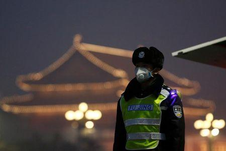 FILE PHOTO: A police officer wears a face mask as he keeps watch in front of Tiananmen Gate on a polluted day in Beijing, China, January 3, 2017. REUTERS/Thomas Peter/File Photo