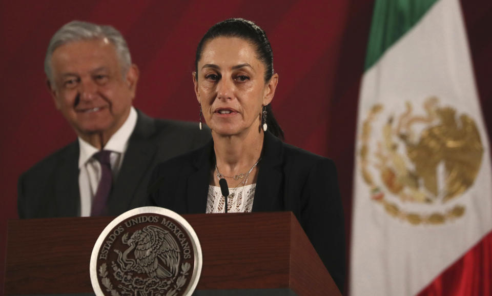 Mexico City's Mayor Claudia Sheinbaum speaks to the press regarding the spread of the new coronavirus, as Mexico's President Andres Manuel Lopez Obrador stand behind during his daily news conference at the presidential palace in Mexico City, early Thursday, March 19, 2020. (AP Photo/Fernando Llano)