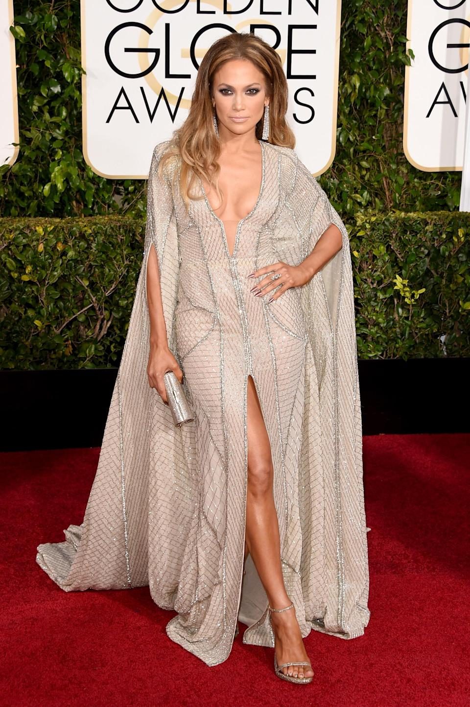 <p>2015 was the year of the cape trend so it makes perfect sense that she would be sporting the trend in true J.Lo fashion: alongside a high-slit and a deep neckline. [Photo: Getty] </p>