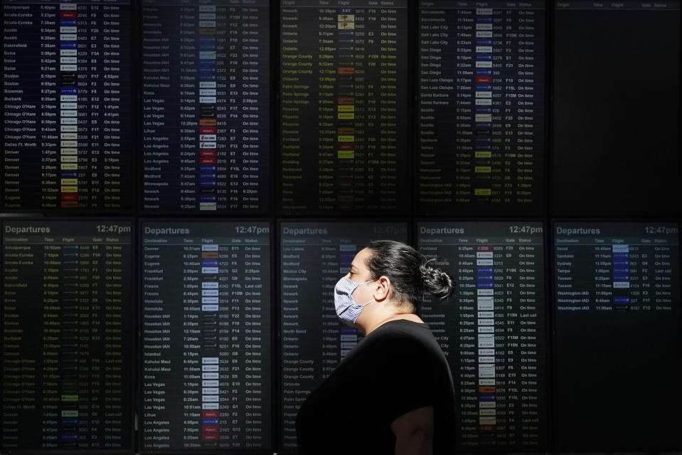 A woman wears a mask while walking past a flight information board at San Francisco International Airport during the coronavirus outbreak in San Francisco, Tuesday, Nov. 24, 2020. (AP Photo/Jeff Chiu)