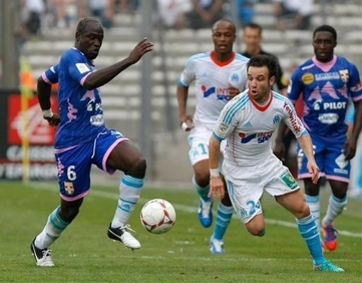 Marseille's French midfielder Mathieu Valbuena, right, challenges Evian's midfielder Djakaridja Kone from Ivory Coast for the ball during their League One soccer match at the Velodrome stadium, in Marseille, southern France, Sunday, Sept. 23, 2012. (AP Photo/Claude Paris)