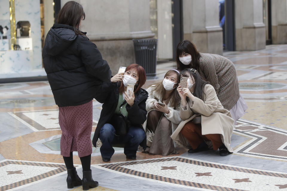 Tourists, wearing face masks, pose for a selfie in downtown Milan, Italy, Thursday, Feb. 27, 2020. In Europe, an expanding cluster in northern Italy is eyed as a source for transmissions of the COVID-19 disease. (AP Photo/Luca Bruno)