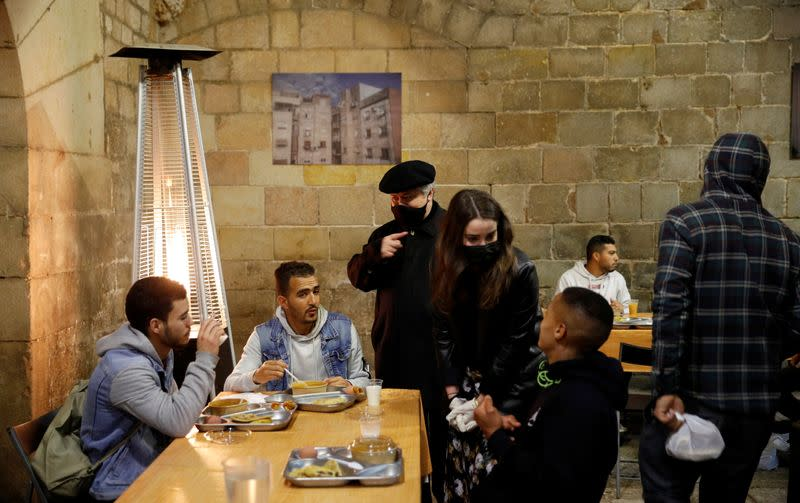 Priest Peio Sanchez speaks with people during a charity Ramadan dinner in the cloister at Santa Anna church in Barcelona