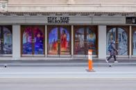 """FILE PHOTO: A woman walks past a """"Stay Safe Melbourne"""" sign on the first day of a seven-day COVID-19 lockdown in Melbourne"""