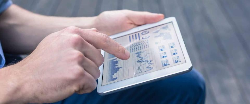 Casual person using digital tablet to analyze financial dashboard with charts.