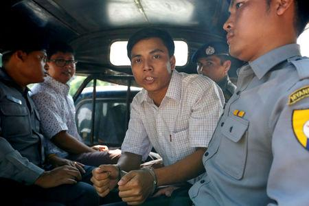 FILE PHOTO: Detained Reuters journalist Kyaw Soe Oo and Wa Lone are transport in a police vehicle after a court hearing in Yangon