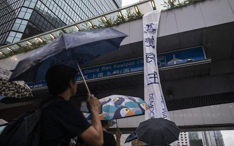 Demonstrators stand around a banner reading 'We Want Democracy' hanging off a pedestrian footbridge on Harcourt Road as rain falls during a protest in the Admiralty district of Hong Kong, China - Credit: Bloomberg
