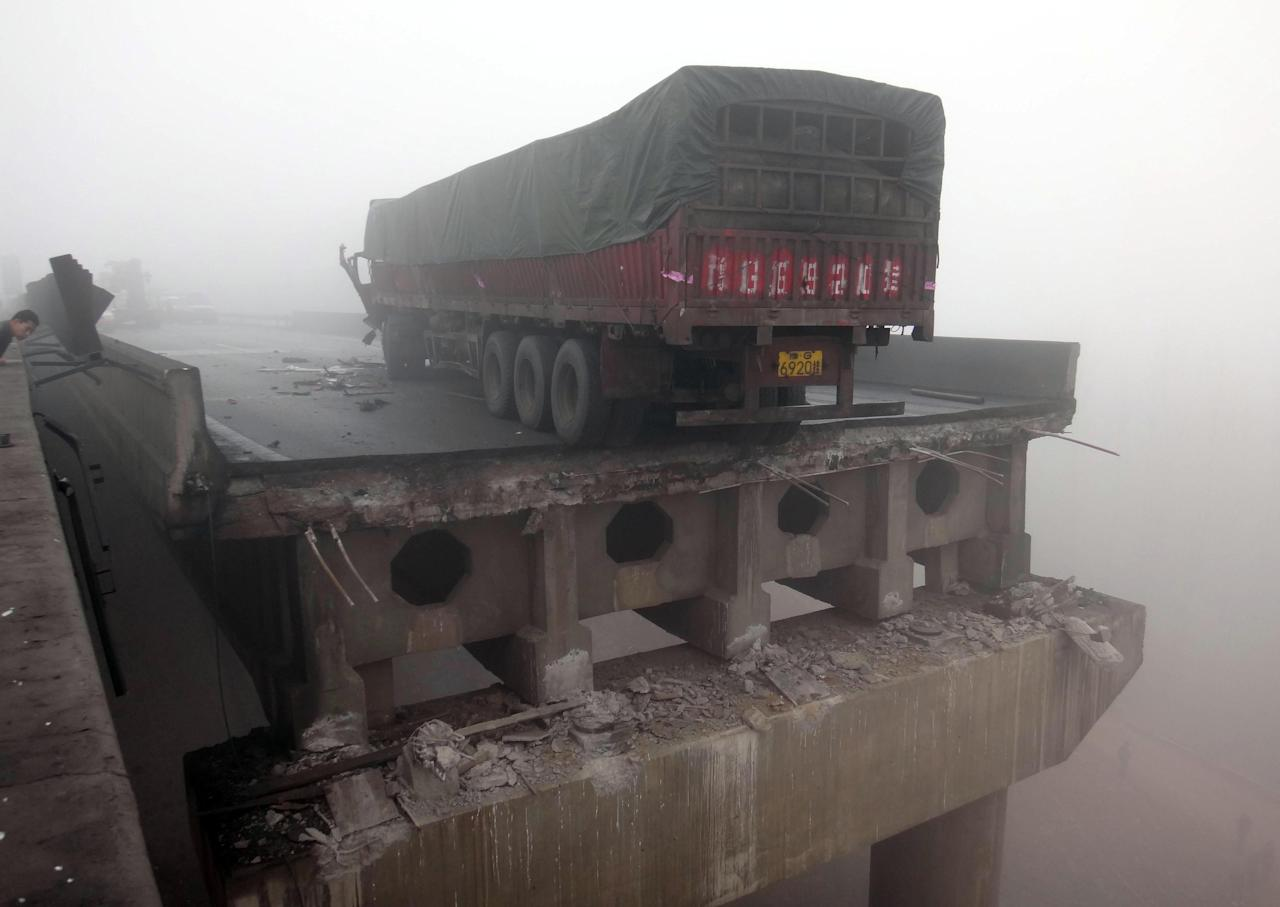 In this photo provided by China's Xinhua News Agency, a truck sits on the expressway bridge which partially collapsed due to an explosion in Mianchi County, Sanmenxia, central China's Henan Province, Thursday, Feb. 1, 2013.  Fireworks for Lunar New Year celebrations exploded on a truck in central China, destroying part of an elevated highway Friday and sending vehicles plummeting 30 meters (about 100 feet) to the ground. (AP Photo/Xinhua, Xiao Meng) NO SALES