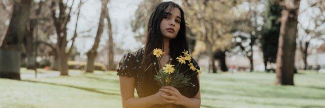 young woman in a dress standing outside holding flowers looking seriously into camera