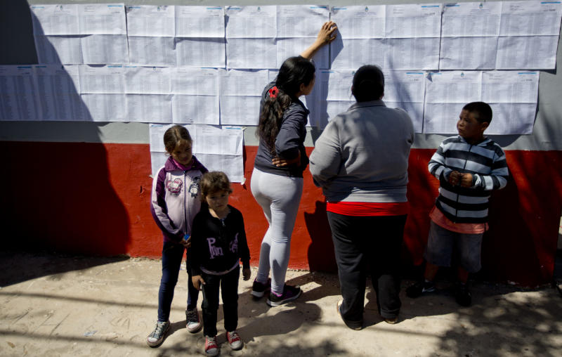 Women look for their names in electoral rolls at a polling station during mid term legislative elections in Buenos Aires' Tigre district , Argentina, Sunday, Oct. 27, 2013. Sunday's run-up to congressional elections will decide how much control President Cristina Fernandez will have over Argentine politics during the final two years of her presidency. (AP Photo/Natacha Pisarenko)