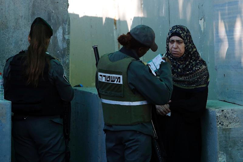 Palestinians are checked at an Israeli checkpoint between the West Bank town of Bethlehem and Jerusalem