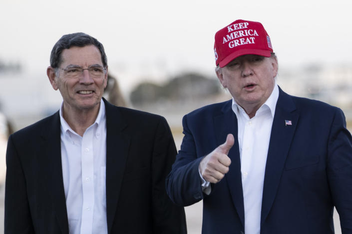President Donald Trump gives thumbs up as he steps off Air Force One, accompanied by Sen. John Barrasso, R-Wyo., at the Palm Beach International Airport, Friday, Nov. 29, 2019, in West Palm Beach, Fla. Trump is returning from a trip to visit the troops in Afghanistan. (AP Photo/Alex Brandon)
