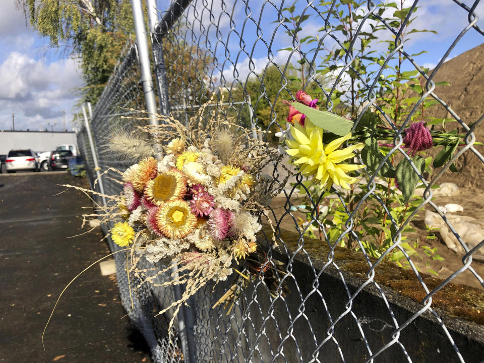 Flowers can be seen tied to a fence in a parking lot in Hazel Dell, Wash., on Friday, Oct. 30, 2020, where a 21-year-old Black man Kevin Peterson Jr. was fatally shot by law enforcement the day before. (AP Photo/Gillian Flaccus)