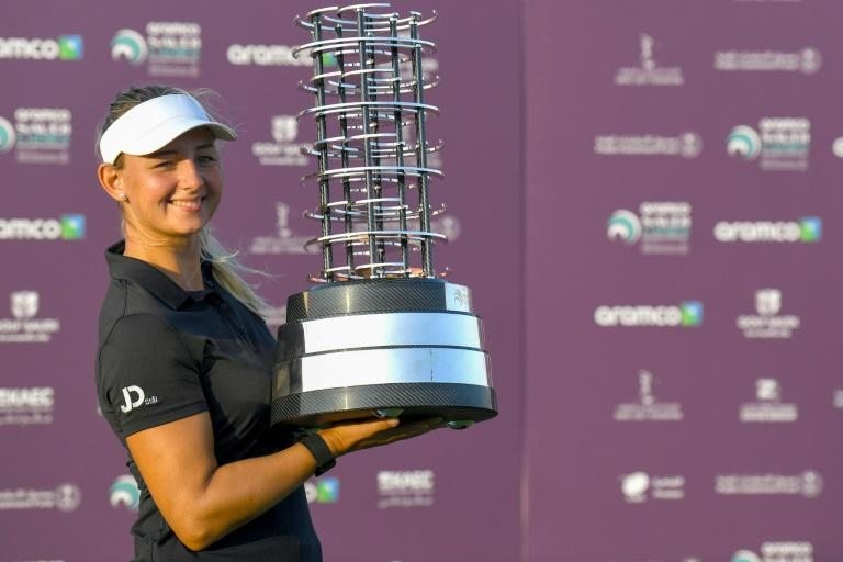 Emily Pedersen celebrates with the trophy after winning the inaugural Saudi Ladies International title