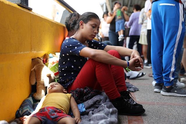 A 17-year-old Honduran mother seeking asylum waits with her 2-year-old son on the Mexican side of the Brownsville-Matamoros International Bridge after being denied entry to the U.S. on July 2. (Photo: Loren Elliott/Reuters)