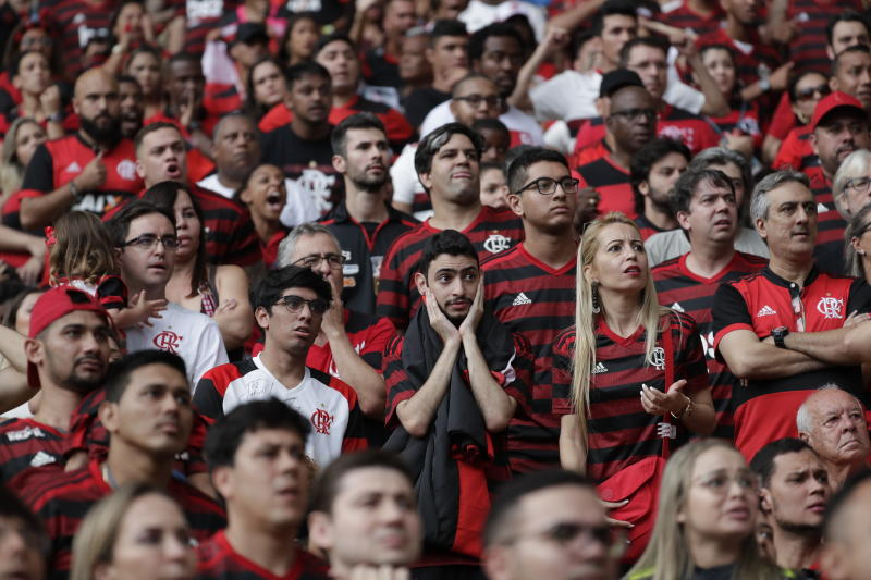 Flamengo soccer fans watch their team go up against Argentina's River Plate in the Copa Libertadores final match, broadcast on a giant screen at a watch party at the Macarena Stadium, in Rio de Janeiro, Brazil, Saturday, Nov. 23, 2019. The first single-match final will be played in front of more than 65,000 fans at Lima's Monumental Stadium. The match was originally scheduled for Santiago's National Stadium, but it was moved because of street protests in Chile. (AP Photo/Silvia Izquierdo)