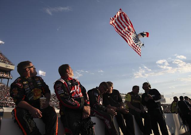 Members of a pit crew watch a parachutist as he comes down with a U.S. flag before the NASCAR Sprint Cup auto race at Richmond International Raceway in Richmond, Va., Saturday, April 26, 2014. (AP Photo/Zach Gibson)