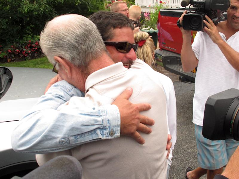 John Aldridge, facing, hugs his father, John Aldridge Sr., after returning to his parents' home, Thursday, July 25, 2013, in Oakdale, N.Y. The younger Aldridge was rescued by the U.S. Coast Guard off the coast of Montauk, N.Y., a day earlier after falling off a lobster fishing boat. Aldridge spent about 12 hours in the water, clinging to a pair of rubber boots to keep him afloat. (AP Photo/Frank Eltman)