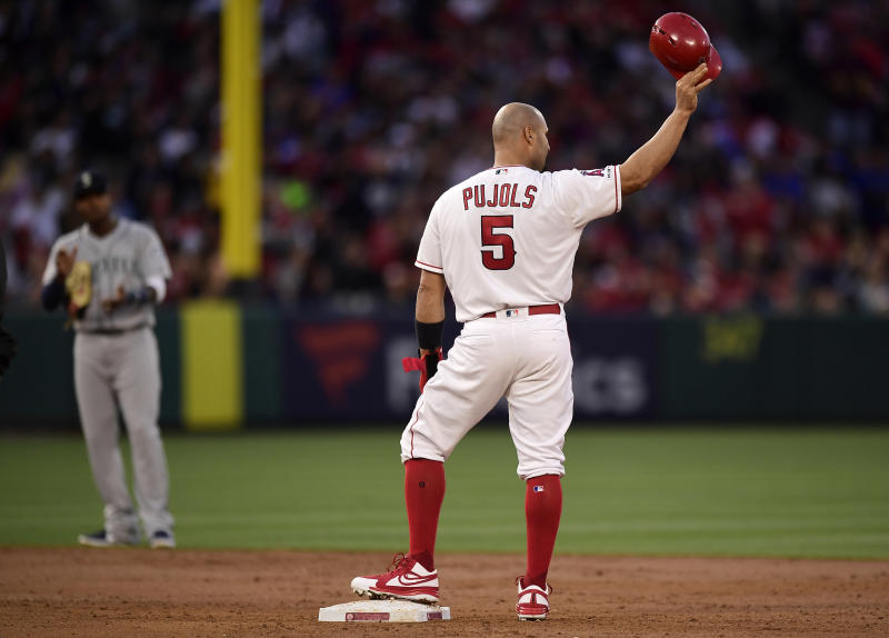 Los Angeles Angels' Albert Pujols, right, tips his helmet to fans after hitting an RBI double as Seattle Mariners shortstop Tim Beckham claps during the third inning of a baseball game Saturday, April 20, 2019, in Anaheim, Calif. With that RBI, Pujols tied Babe Ruth for 5th place on the all-time RBI list with 1,992. (AP Photo/Mark J. Terrill)