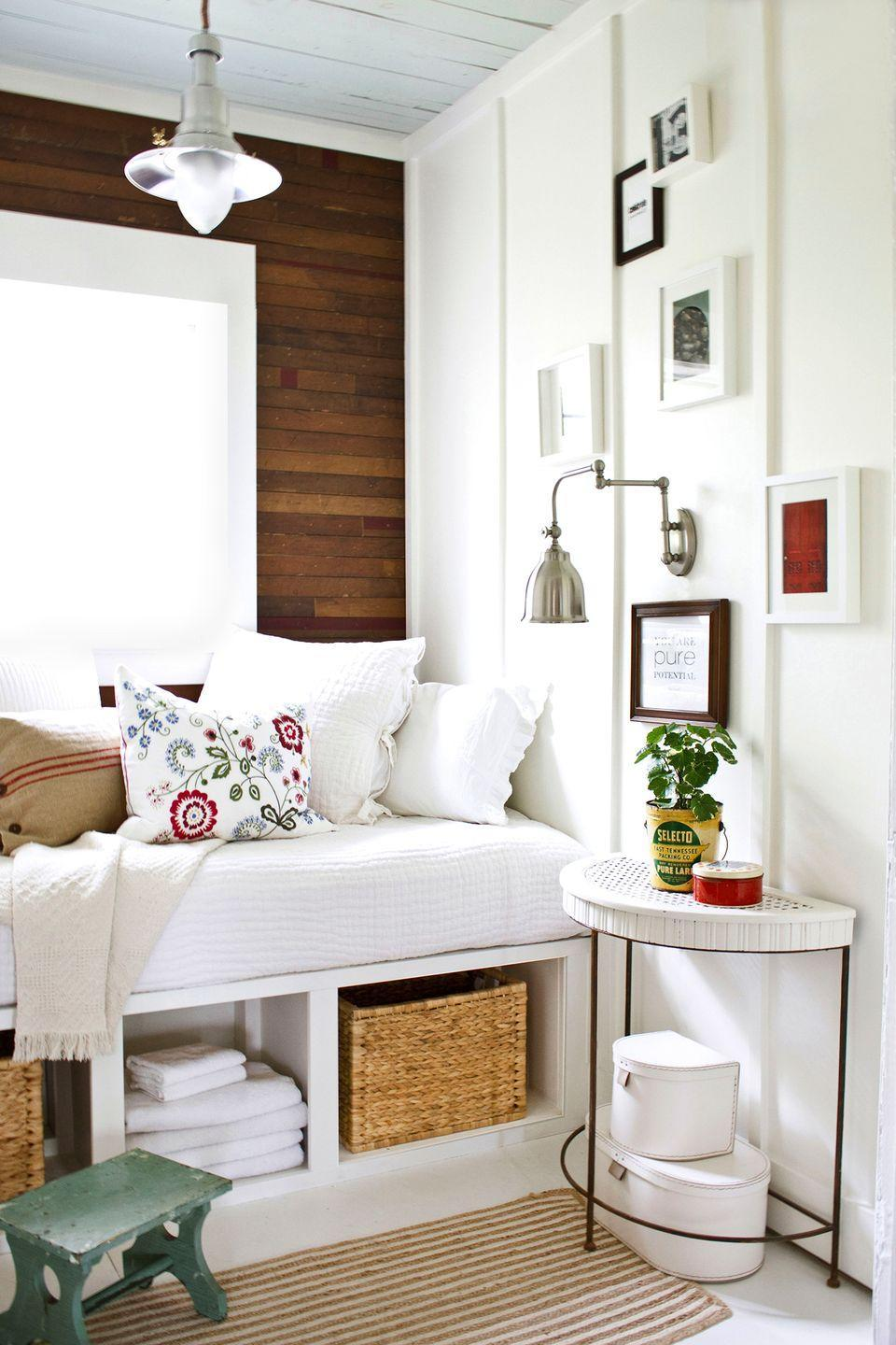 <p>Natural accents, including a wood paneled wall and woven storage basket, bring warmth to this white reading nook. </p>