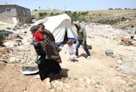 A Palestinian family, whose house was demolished by Israeli bulldozers, walk past a tent in the southern West Bank village of Ad-Deirat Rifaiyya on April 21, 2015 (AFP Photo/Hazem Bader)