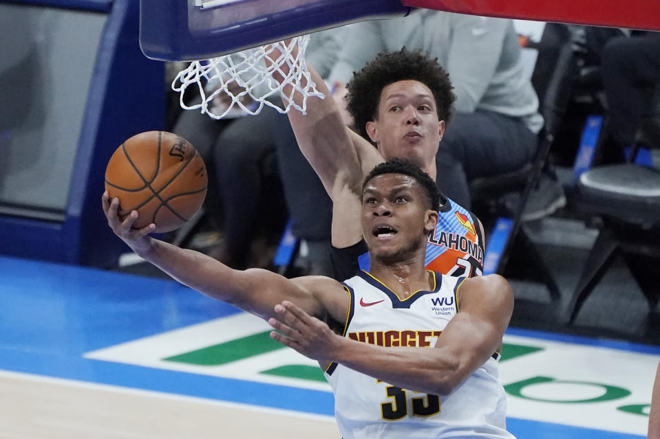 Denver Nuggets guard PJ Dozier (35) shoots in front oof Oklahoma City Thunder center Isaiah Roby during the second half of an NBA basketball game Saturday, Feb. 27, 2021, in Oklahoma City. (AP Photo/Sue Ogrocki)