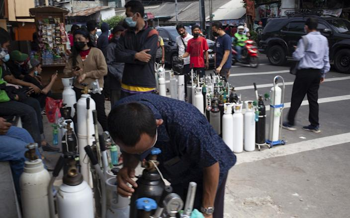 People queue up to refill their oxygen tanks at a filling station in Jakarta - Anadolu