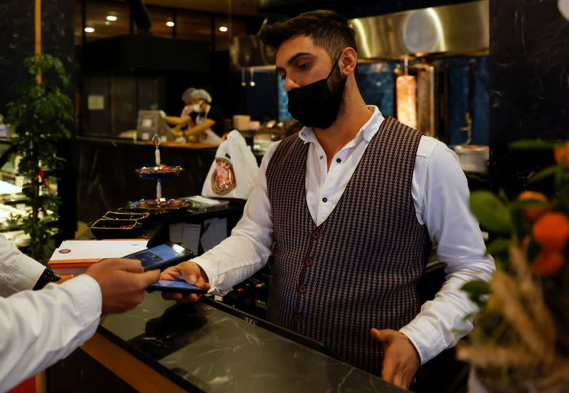 glA cashier recieves a payment via a cryptocurrency app at a kebab restaurant that accepts Bitcoin and Dexchain in Istanbul