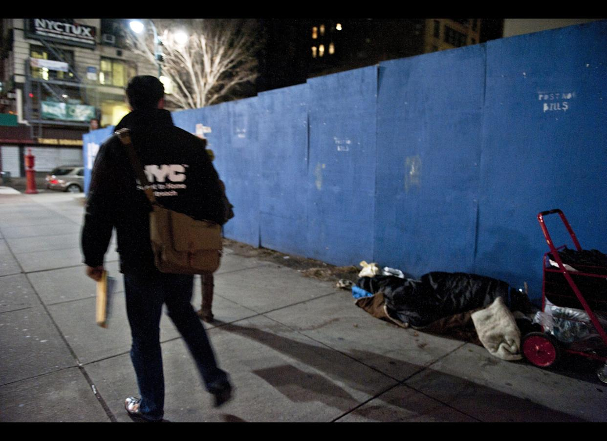 Volunteers along with members of the New York City Department of Homeless Services walk by a homeless person sleeping on the street. The New York City DHS assisted by volunteers put on a homeless count in the borough of Manhattan's Murray Hill neighborhood Jan. 30, 2012. (Damon Dahlen, AOL)