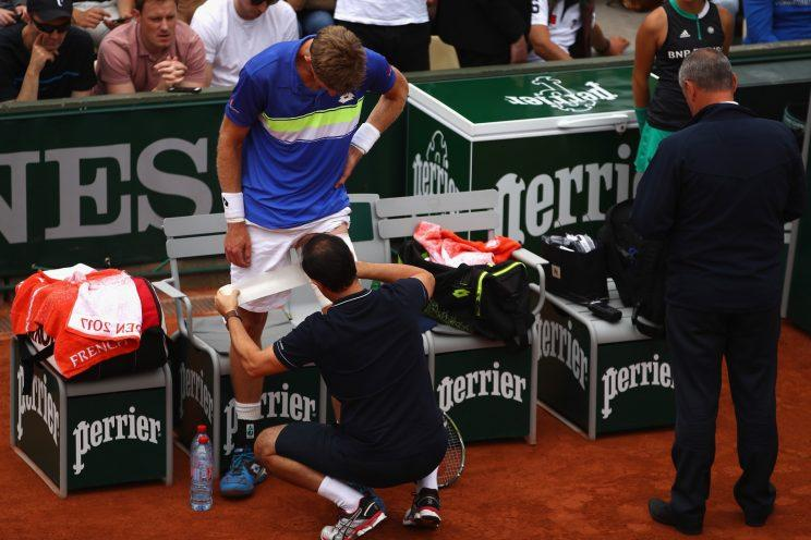 South African tennis player Kevin Anderson receives treatment and support for an injury in the third round of the French Open. Injuries ultimately forced Anderson to resign from the tournament one match later. (Getty Images)