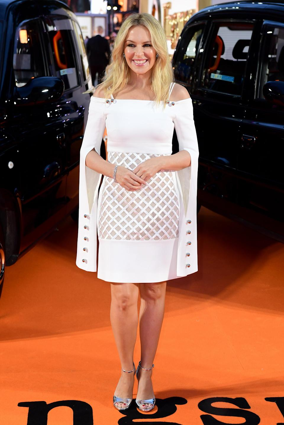 <p>Kylie Minogue made a surprise appearance in a white caped dress by London Fashion Week designer David Koma.<br><i>[Photo: PA]</i> </p>