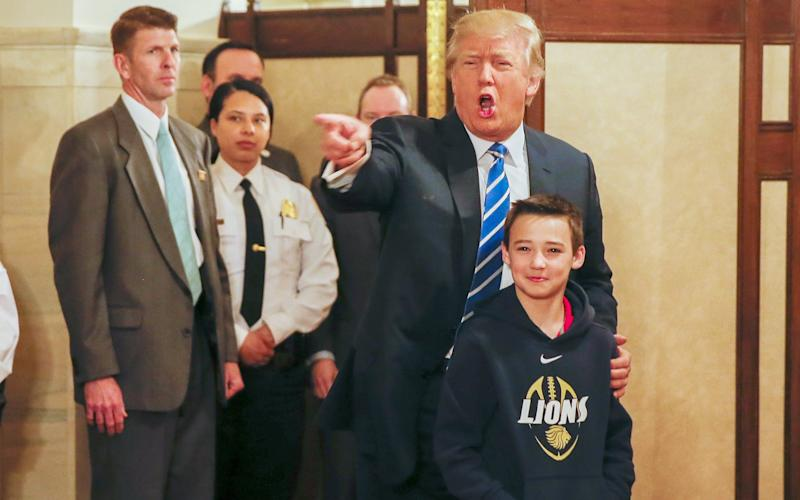 10-year-old Jack Cornish, from Alabama, poses for a photo with Trump - Credit: ERIK S. LESSER/EPA