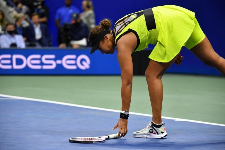Japan's Naomi Osaka retrieves the racquet she tossed in her upset loss to Leylah Fernandez at the US Open (AFP/Ed JONES)