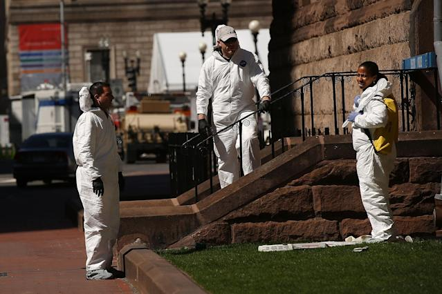BOSTON, MA - APRIL 17: Members of the Federal Bureau of Investigation (FBI) search for clues near the scene of twin bombings at the Boston Marathon on April 17, 2013 in Boston, Massachusetts. The explosions, which occurred near the finish line of the 116-year-old Boston race on April 15, resulted in the deaths of three people with more than 170 others injured. Security has been heightened across the nation as the search continues for the person or people behind the bombings. (Photo by Spencer Platt/Getty Images)