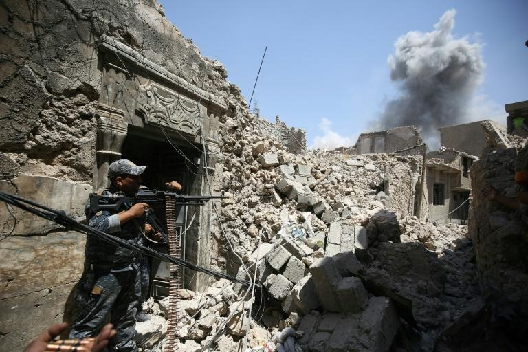 Members of the Iraqi federal police hold position during an armed exchange in the Old City of Mosul on June 28, 2017 as smoke billows in the background