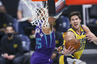 Indiana Pacers forward Doug McDermott, right, drives to the basket against Charlotte Hornets forward P.J. Washington during the first half of an NBA basketball game in Charlotte, N.C., Wednesday, Jan. 27, 2021. (AP Photo/Nell Redmond)