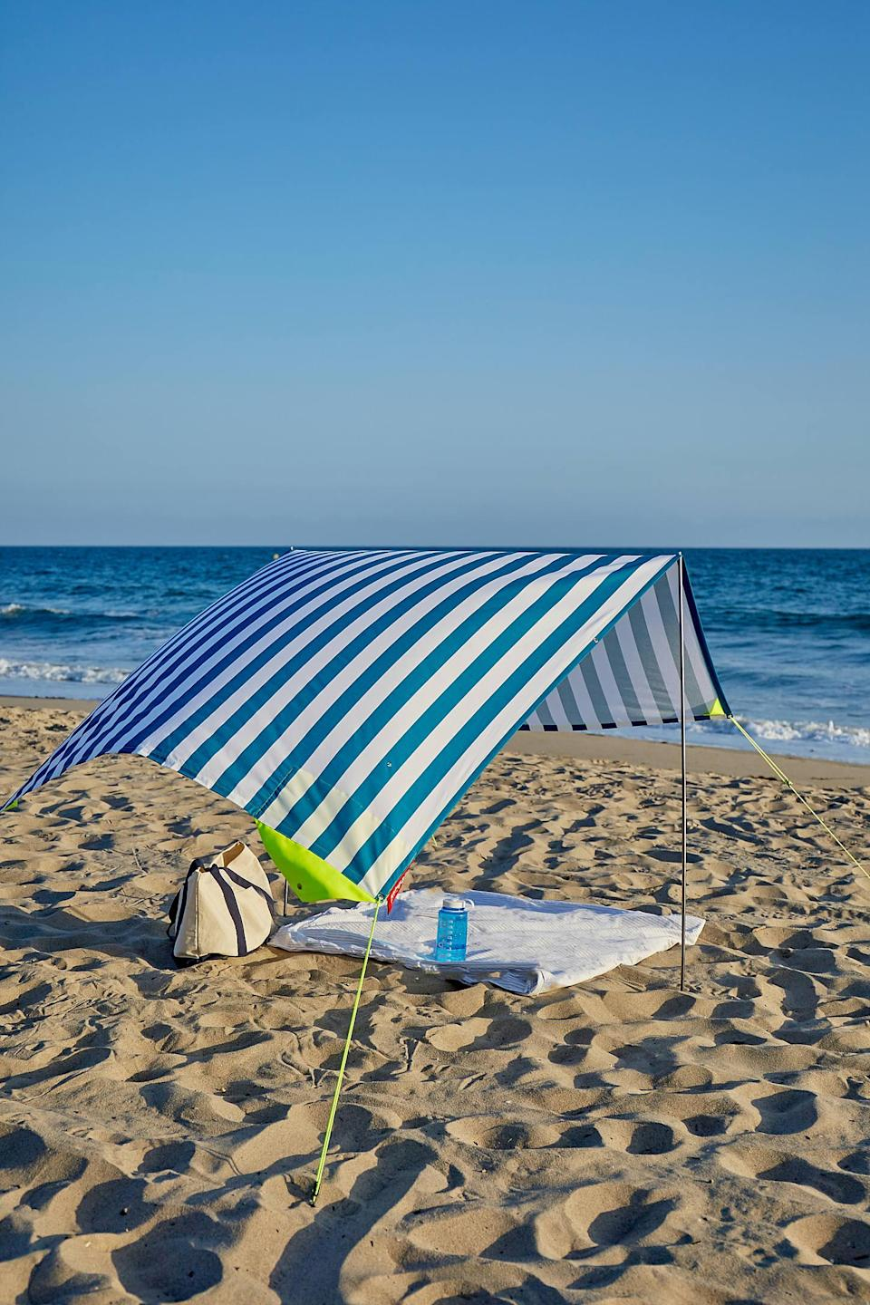 """This eye-catching sun shelter is ideal for clear-skied beach days, with a cotton shade that comes in seven sunny colorways so that your friends can find you easily when its time to meet up. <br> <br> <strong>Fatboy</strong> UV Filter Portable Beach Tent, $, available at <a href=""""https://go.skimresources.com/?id=30283X879131&url=https%3A%2F%2Fwww.urbanoutfitters.com%2Fshop%2Ffatboy-x-miasun-uv-filter-portable-beach-tent"""" rel=""""nofollow noopener"""" target=""""_blank"""" data-ylk=""""slk:Urban Outfitters"""" class=""""link rapid-noclick-resp"""">Urban Outfitters</a>"""