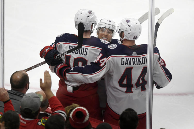 Columbus Blue Jackets' Pierre-Luc Dubois (18) celebrates with teammates Cam Atkinson (13) and Vladislav Gavrikov (44) of Russia, after scoring a goal during the second period of an NHL hockey game against the Chicago Blackhawks, Friday, Oct 18, 2019, in Chicago. (AP Photo/Paul Beaty)