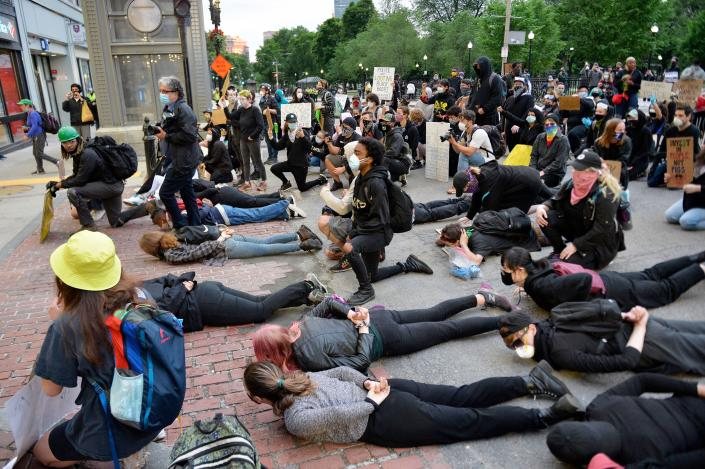 Protesters lie down to block Tremont Street in a small standoff with police after a larger protest to call for Police Department reform in Boston, Massachusetts on June 7, 2020. - Protesters have rallied for racial justice in cities across the United States following the death of George Floyd at the hands of police on May 25. (Photo by Joseph Prezioso / AFP)